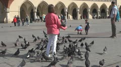 People with pigeons in Market Square, Old Town,Krakow, Poland Stock Footage