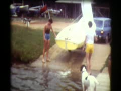 70's family Launching sailboat in lake Stock Footage