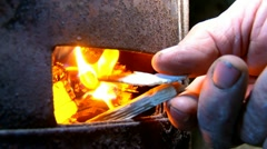 Old man ignited a fire in a metal stove Stock Footage