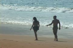 Couple walk on beach - stock footage