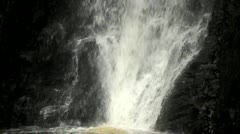 A close up of a waterfall flowing into a pool followed by a slow tilt upward. - stock footage