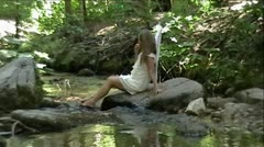 Angel Eating Apple in Mountain Creek and Forest Stock Footage