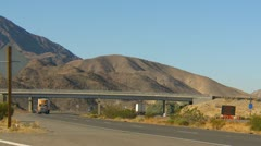 Transport trucks in the desert around bend with overpass Stock Footage