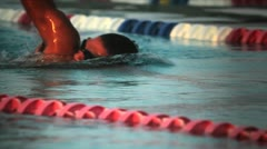 Side view of a swimmer in lanes in a pool. Stock Footage