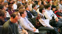 Listeners in hall attentively look at conferences and write down - stock footage