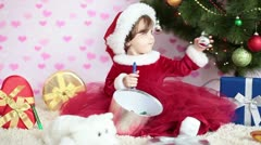 Baby girl with xmas gifts sitting near a Christmas tree Stock Footage