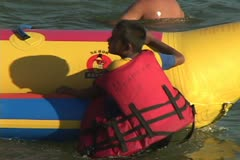 Young riders get settled on a Banana Tube water ride. Stock Footage
