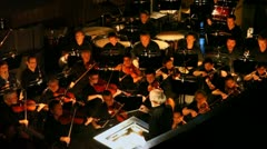 Orchestra in pew plays under direction of Evgenie Samoilov at New Opera Theatre - stock footage
