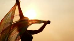 Woman against sky and sun has hold thin shawl which waves Stock Footage