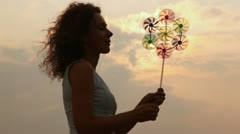 childrens windmill to turn on wind at woman in hands - stock footage