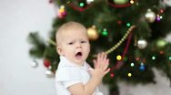 Stock Video Footage of Baby girl yawns beside the Christmas Tree