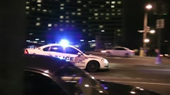 Police car races down city street, DC, night Stock Footage