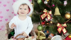 Laughing baby in santa hat standing in a basket near the Christmas tree Stock Footage