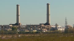Power plant in the desert, distant, twin stacks Stock Footage