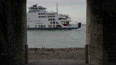 Vehicle ferry arrives in Portsmouth harbour as seen through castle walls Stock Footage