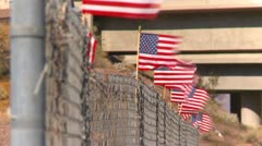 US flags on a chain link fence LS - stock footage