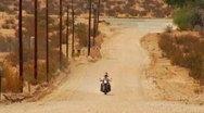 Motorcycle On Dirt Road In Desert 1 Stock Footage