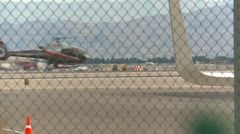 Helicopter AStar taxi hover beyond fence Stock Footage