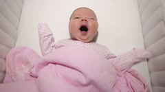 Baby laying in the crib and yawning Stock Footage