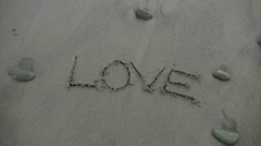 'love' washed away on the beach Stock Footage