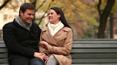 happy couple joking on park bench - stock footage