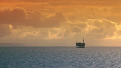 Ocean sunset - oil rig drilling platforms on horizon Stock Footage