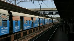 A busy commuter train leaves a station in Mumbai, India Stock Footage
