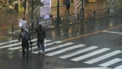 Crosswalk on a street in Tokyo during a typhoon. - stock footage