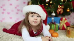 Baby girl in a santa hat lying on the floor. Looking at camera. Slow motion Stock Footage