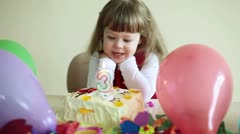 Child is birthday. Baby sitting at the table and make a wish Stock Footage