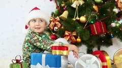 Girl in santa hat sitting beside a Christmas tree Stock Footage