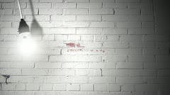 LOOPING Light bulb on white bricks  - stock footage