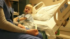 Nurse checking on child in hospital bed HD8481 Stock Footage