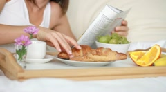 Woman eating breakfast in bed and reading magazine, dolly shot HD - stock footage