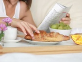 Woman eating breakfast in bed and reading magazine, dolly shot NTSC Stock Footage