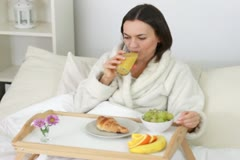 Attractive happy woman eating breakfast in bed NTSC Stock Footage