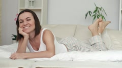 Attractive happy woman lying in bed, dolly shot HD - stock footage