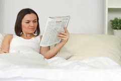 Woman drinking coffee in bed and reading magazine, dolly shot NTSC Stock Footage