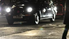 People Crossing street at night infront of taxi in london Stock Footage