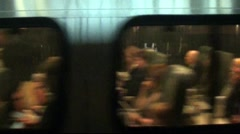Train passengers traveling - see through window, leaving station Stock Footage