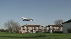 Airliner flies low over houses Stock Footage