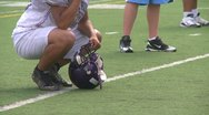 Football player squatting on sidelines Stock Footage
