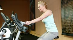 Woman using hometrainer in fitness center Stock Footage