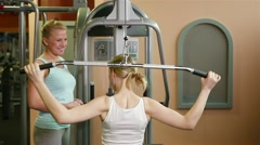 Fitness trainer explaining lat machine in gym Stock Footage