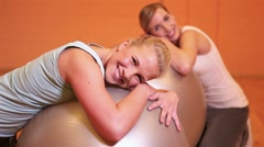 Women relaxing after workout on gym ball Stock Footage