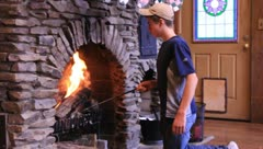 Teen boy pokes at fire in a fireplace (HD) co Stock Footage