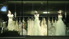 Stock Video Footage of Wedding Dress shopping manicans in the window