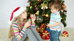 Sister and brother near the Christmas tree. Girl blowing bubbles Stock Footage