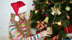 Happy girl with a Christmas gift in his hands looking at camera - stock footage