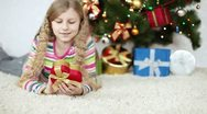 Girl considering a Christmas gift and lying on the floor near Christmas Tree. Stock Footage